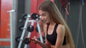 Sorriso bonito da moça e smartphone dos usos ao descansar no banco após seu treinamento intensivo video estoque