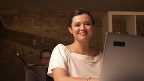 Sorriso bonito da mulher caucasiano que senta e que olha seu portátil, trabalhando no escritório do tijolo com associado atrás filme