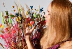 Sorriso bonito da mulher com o ramalhete da opinião superior de sorriso feliz do retrato do close up das flores selvagens no cinz Foto de Stock Royalty Free