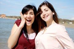 Sorriso bonito das meninas feliz na frente do mar fotografia de stock