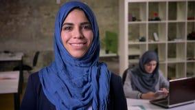Sorriso bonito focalizado em face da mulher árabe em escuro - hijab azul que está no escritório moderno, realidade hoje em dia vídeos de arquivo