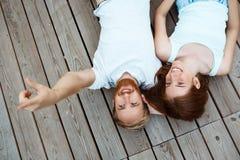 Sorriso bonito novo dos pares, encontrando-se em placas de madeira Disparado de cima de Imagem de Stock