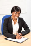 Sorriso bonito pela mulher preta no escritório de negócio Fotografia de Stock