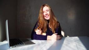Sorriso caucasiano da menina à câmera com ondulações e portátil em casa video estoque