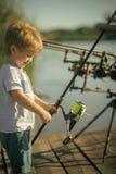 Sorriso da criança com a vara de pesca no cais de madeira fotografia de stock royalty free