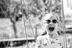 Sorriso da criança pequena no balanço na jarda do verão A menina da forma nos óculos de sol aprecia balançar no dia ensolarado So fotografia de stock royalty free