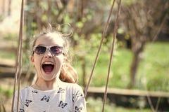 Sorriso da criança pequena no balanço na jarda do verão A menina da forma nos óculos de sol aprecia balançar no dia ensolarado So imagem de stock royalty free