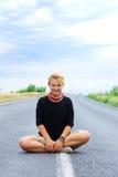 Sorriso da jovem mulher na posição dos lótus sobre a estrada Fotos de Stock