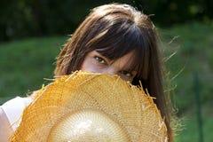 Sorriso da mulher escondido atrás de um chapéu de palha fotografia de stock royalty free
