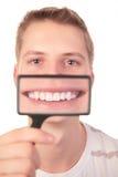 Sorriso das mostras do homem através do magnifier fotos de stock