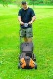 Sorriso de sega da grama do homem Fotografia de Stock