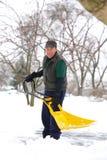 Sorriso de trabalho com pá da neve do homem Imagens de Stock Royalty Free