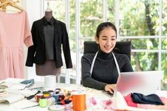 Sorriso de vista esperto asiático feliz do desenhador de moda, sentando-se no estúdio moderno do escritório imagem de stock royalty free