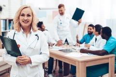 Sorriso del ` s di medico delle donne bianche Riunione diagnostica immagini stock libere da diritti