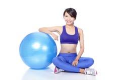 Sorriso della donna che si siede con la palla dei pilates Fotografia Stock