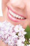 Sorriso della donna con i fiori Fotografia Stock