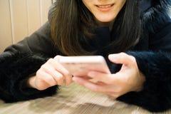 Sorriso della giovane donna di Socialholic al suo Smart Phone Fotografie Stock Libere da Diritti
