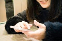 Sorriso della giovane donna di Socialholic al suo Smart Phone Fotografia Stock Libera da Diritti