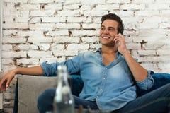 Sorriso di telefonata dell'uomo, seduta di comunicazione Fotografie Stock