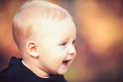 Sorriso do bebê na natureza borrada Pouco criança com o cabelo louro exterior Criança com cara adorável Infância feliz imagens de stock royalty free