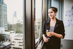 Sorriso e condizione della donna di affari alla finestra con champagne immagine stock