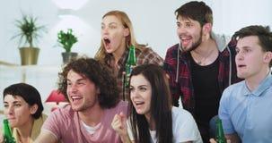 Sorriso e grupo concentrado feliz de amigos que olham um fósforo de futebol excitaram gritar e elogios com cerveja video estoque