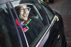 Sorriso e homem de negócios feliz que olham através da janela de carro na noite fotos de stock royalty free