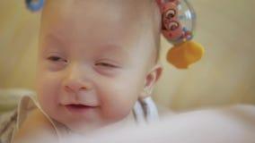 Sorriso e jogo felizes do bebê com os brinquedos que encontram-se na cama Feche acima dos 5 meses adoráveis do laughin velho do b filme