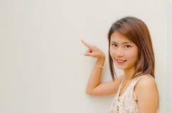 Sorriso e punto della ragazza su priorità bassa bianca Fotografia Stock