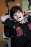 Sorriso e relaxi biracial do menino da criança de oito anos deficiente considerável Imagem de Stock