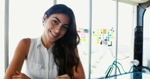 Sorriso executivo fêmea na mesa no escritório 4k video estoque