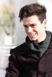 Sorriso exterior do menino novo com revestimento e lenço Fotografia de Stock Royalty Free