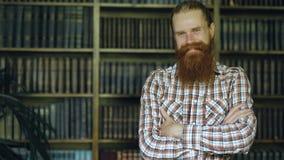 Sorriso farpado novo do homem do retrato feliz na biblioteca e vista na câmera filme