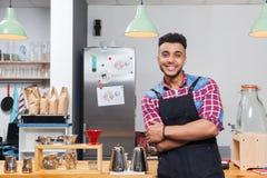 Sorriso felice dell'uomo bello del proprietario di caffetteria di barista che si siede sulla barra fotografia stock