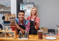 Sorriso felice delle coppie del proprietario di caffetteria di barista al contatore della barra immagini stock