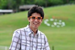Sorriso feliz dos óculos de sol alaranjados do homem de Ásia Tailândia imagem de stock royalty free