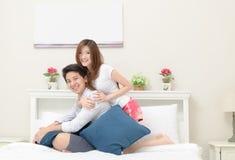 Sorriso feliz dos pares e assento na cama, foto de stock royalty free