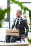 Sorriso homem de negócios fisicamente deficiente com os dobradores no escritório Fotografia de Stock