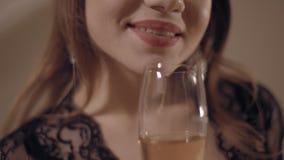 Sorriso incantante di giovane donna sensuale che tiene il bicchiere di vino con vino rosato video d archivio