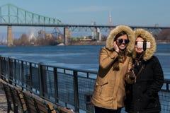 Sorriso jovens mulheres calorosamente vestidas que tomam um selfie no porto velho de Montreal's foto de stock