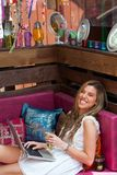 Sorriso louro com portátil e copo de chá no sofá. Fotografia de Stock Royalty Free