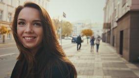 Sorriso modelo na roupa ocasional que anda na cidade do outono filme