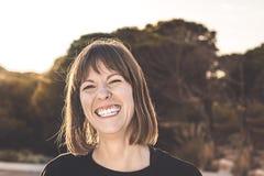 Sorriso moreno normal da menina Mulher com um sorriso em um por do sol foto de stock royalty free