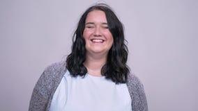 Sorriso obeso e risata caucasici stupefacenti della ragazza che stanno macchina fotografica vicina su fondo grigio video d archivio