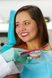 Sorriso paciente da mulher bonita quando o doutor escovar uma chapa dental falsificada em um escritório do ` s do dentista foto de stock royalty free