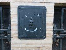 Sorriso pintado em uma porta pequena do ferro fundido em uma parede de pedra fotografia de stock