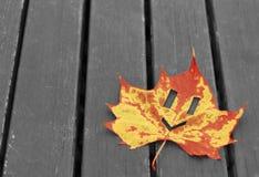 Sorriso sulla foglia di acero su fondo di legno, concetto di buon umore, fondo di autunno, spazio della copia immagini stock libere da diritti