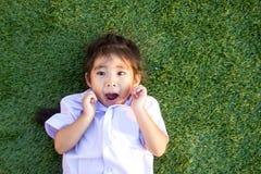 sorriso tailandês asiático das crianças na grama verde Imagens de Stock Royalty Free