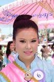 sorriso tailandês da senhora do ⢠na parada do pedal uma bicicleta. Imagens de Stock