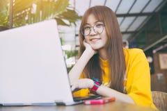 Sorriso teenager dei pantaloni a vita bassa del nerd di vetro con il computer portatile del computer Fotografia Stock
